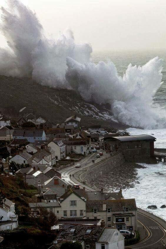 A wave crashes over the cliffs at Sennen Cove in Cornwall, England, UK.