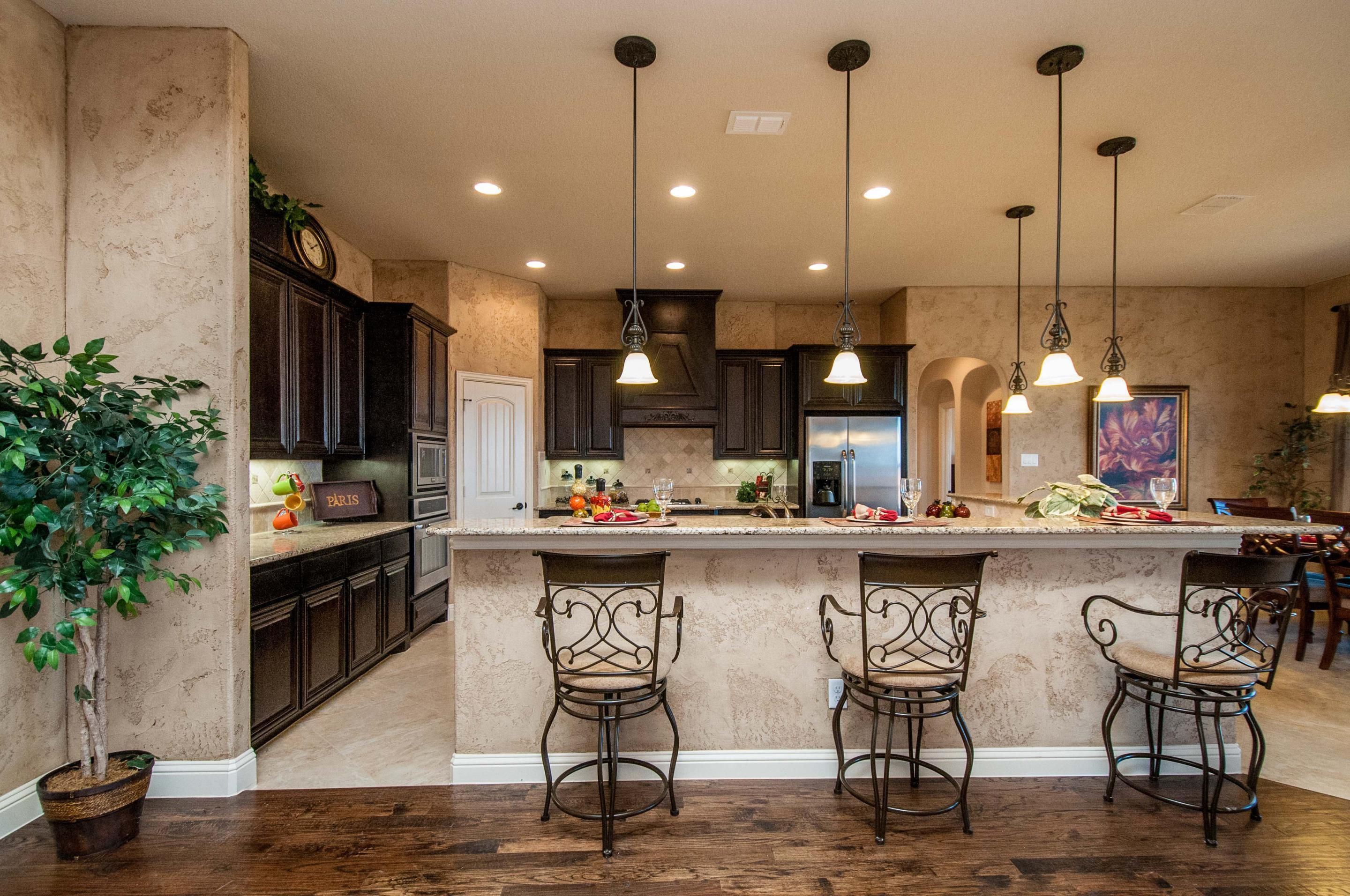 Dark Accents In A Gleaming Wood Floor Complement The Cabinetry And Colors Throughout This Kitchen New Homes From Lillian Custom Near Dallas Ovilla