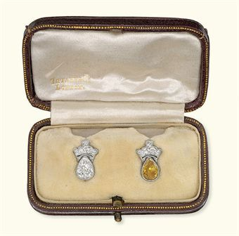 A PAIR OF DIAMOND EAR STUDS -Each designed as either a pear-shaped white or orangy-yellow diamond to the old-cut diamond coronet surmount, in later fitted case