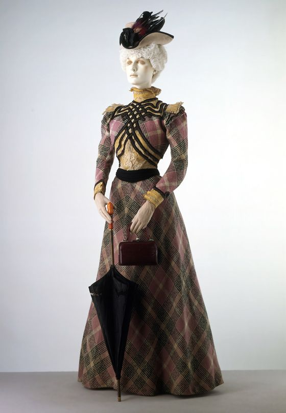 Pinned Image Walking dress, 1895-1900. Every line in this dress emphasize the tiny waistline. This is skillful fashion design at its peak. Note how the wide ribbon trim seperates and cuts out the bustline, making it look wider, and how the slight slant of the black waistband elongates the torso and slenders the waist.