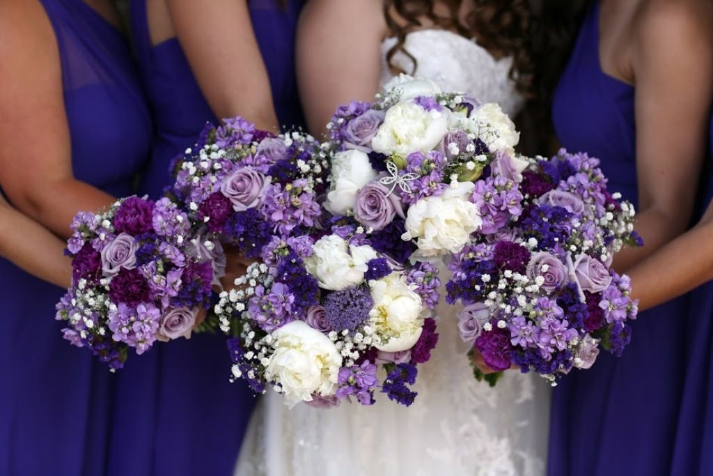 Purple and white bridal party flowers from Seasonal Celebrations. Bridal bouquet with peonies (top), MOH with peony (bottom) and bridesmaids. Photo courtesy of Marielle Hayes Photography.