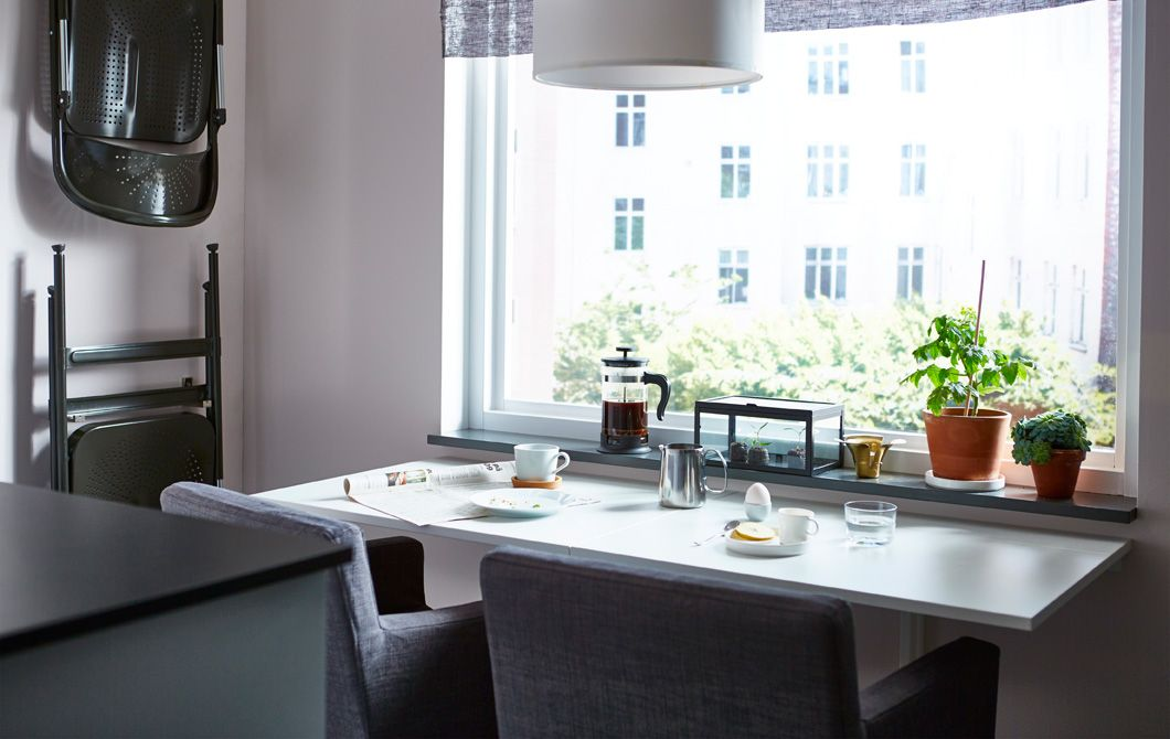 Spisebord med 2 spisestuestole, der vender ud mod et vindue ...