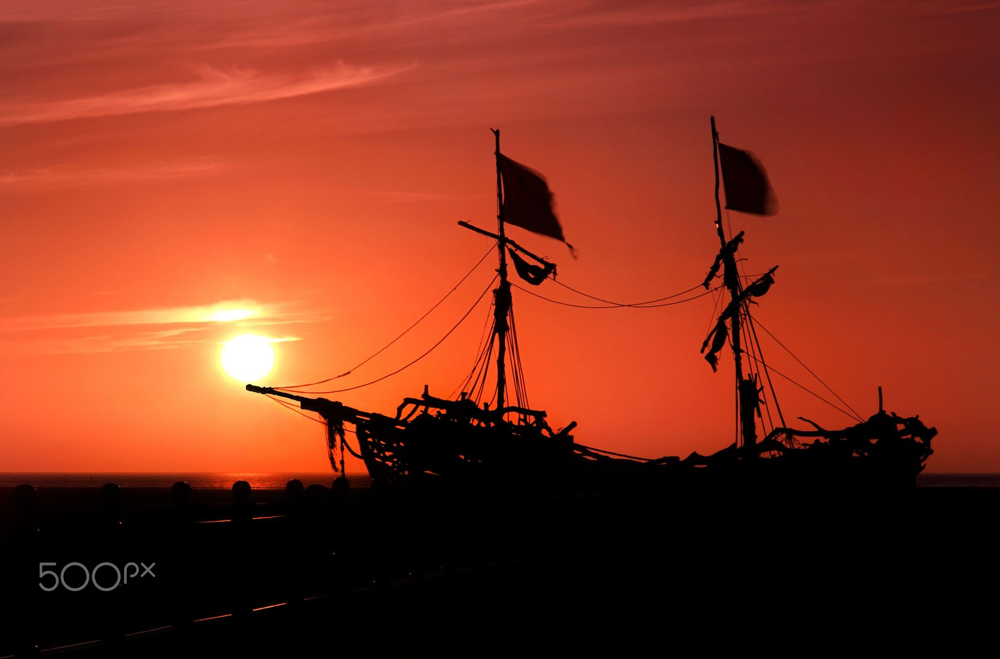 Pirate Sunset - As the sun slowly sets for a moment it is captured resting on the bow of the Grace Darling Pirate Ship in Hoylake on The Wirral Peninsula
