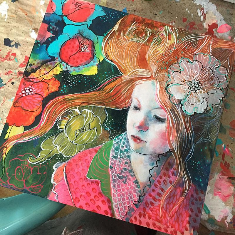 Mixed Media Painting of a girl with long red hair in a red spotty dressing gown surrounded by beautiful red flowers. The girl has a white flower in her hair. Painting by Maria Pace-Wynters