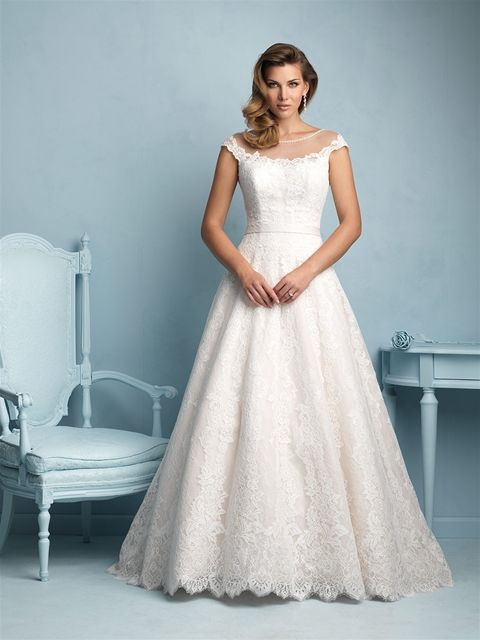 Allure Bridals 9222   A strand of Swarovski crystals run across the sheer illusion neckline of this lace A-line gown.The graceful silhouette is emphasized by a scooped back and cap sleeves.