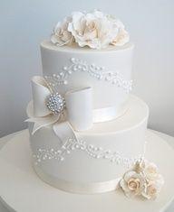 Bolo de casamento branco com textura, flores e laço.