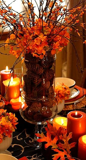 Leaves and orange candles make for the perfect intimate for Thanksgiving centerpieces with candles