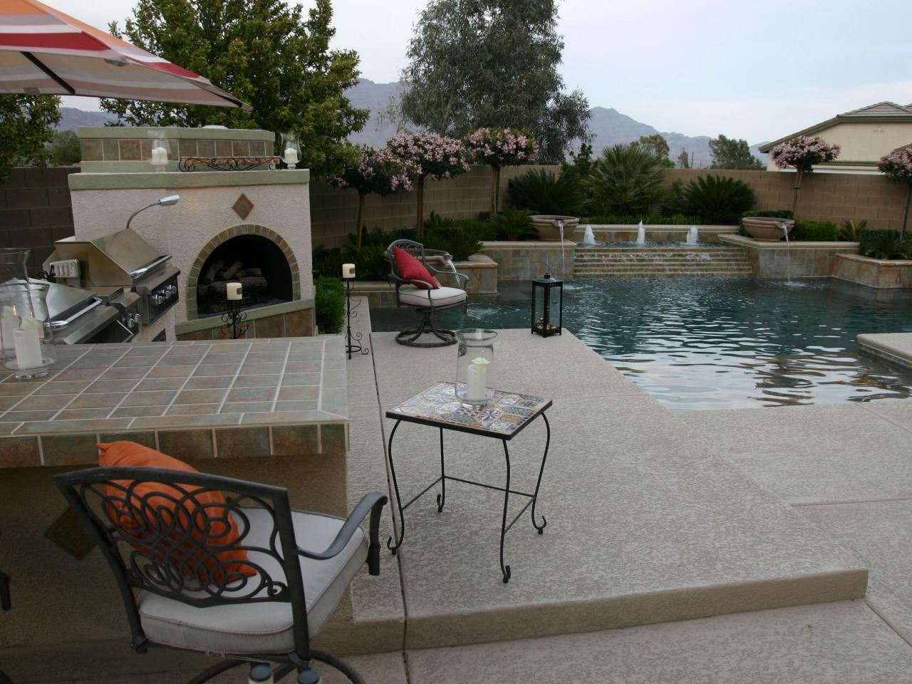 A full backyard entertainment area with an outdoor kitchen is complete with a barbecue and hearth. The neutral tile on the fireplace complements the Mediterranean-style design of this pool and spa.