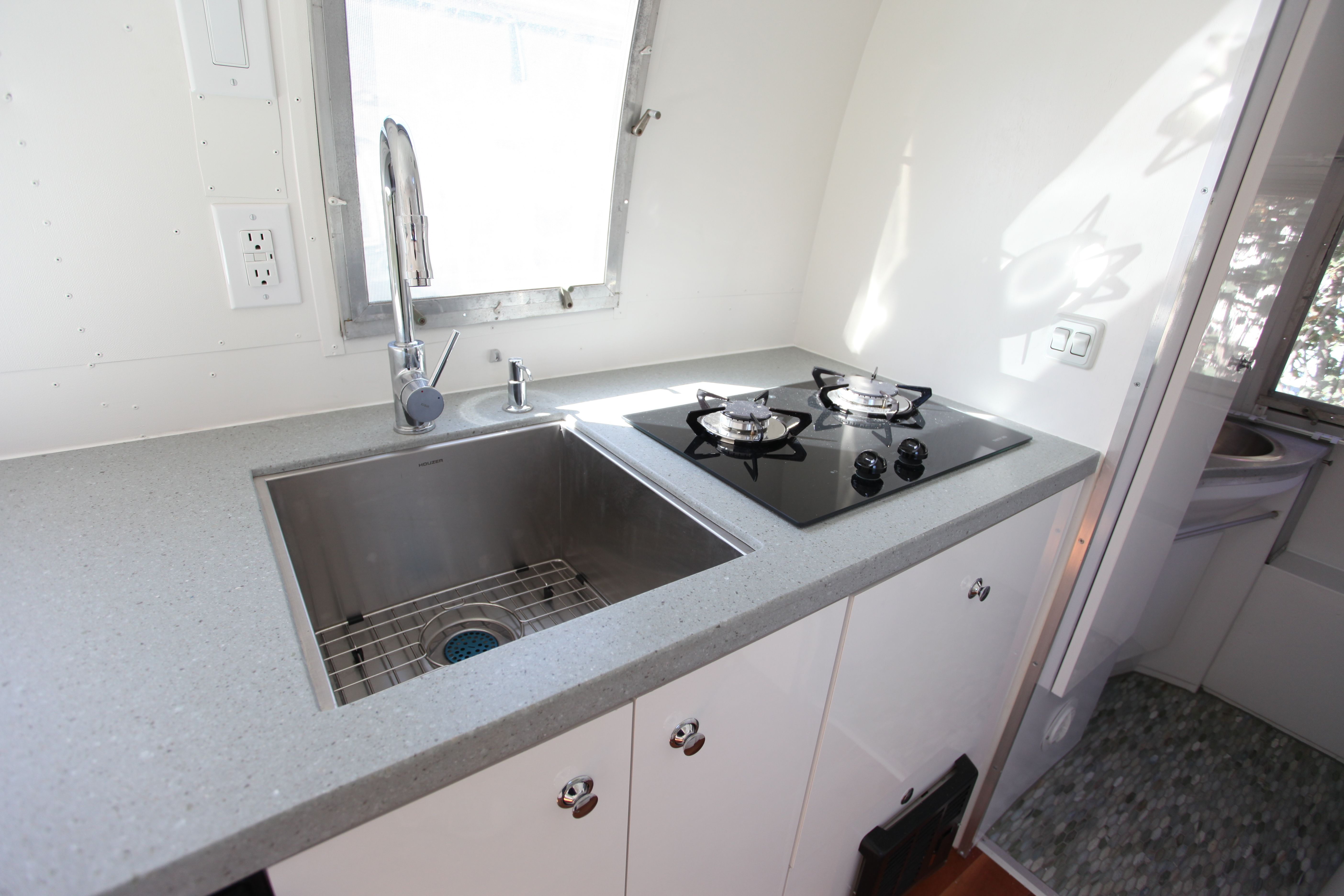 Light Grey Corian Countertops, A Stainless Steel Sink And Faucet, Help Keep  The Clean