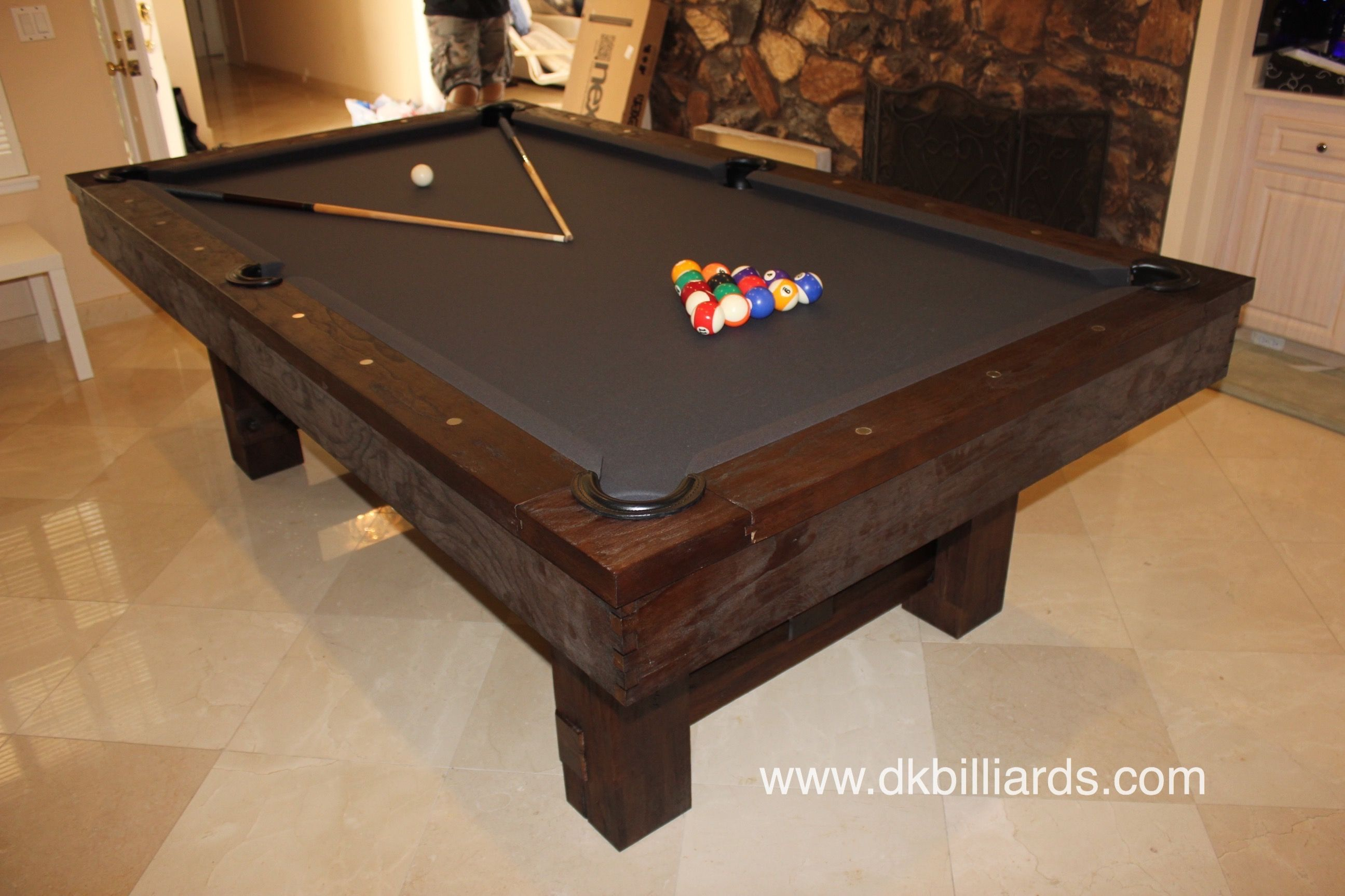 The dark stained scraped wood finish of this 8′ rustic pool table