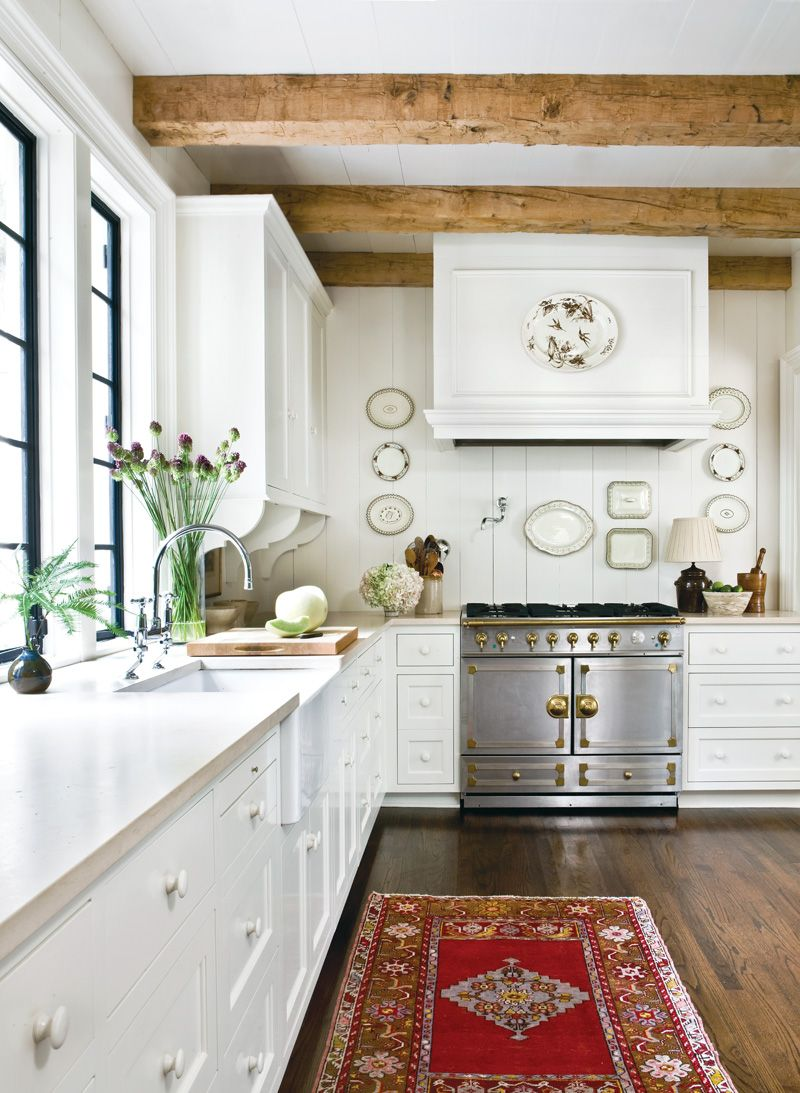 Love the stove..dark wood floors, lighter wood beams...white/cream ...