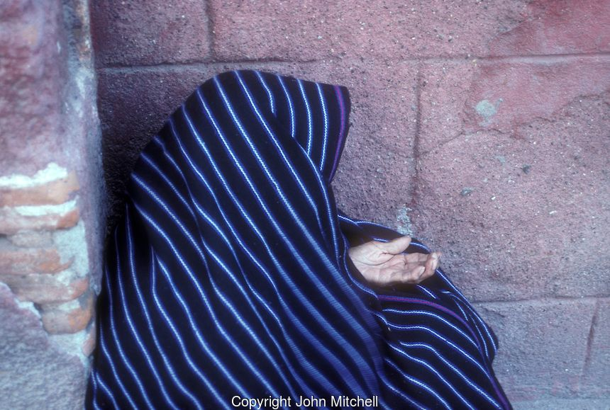 Elderly woman wearing a woven Mexican rebozo begging on the street in San Miguel de Allende, Mexico