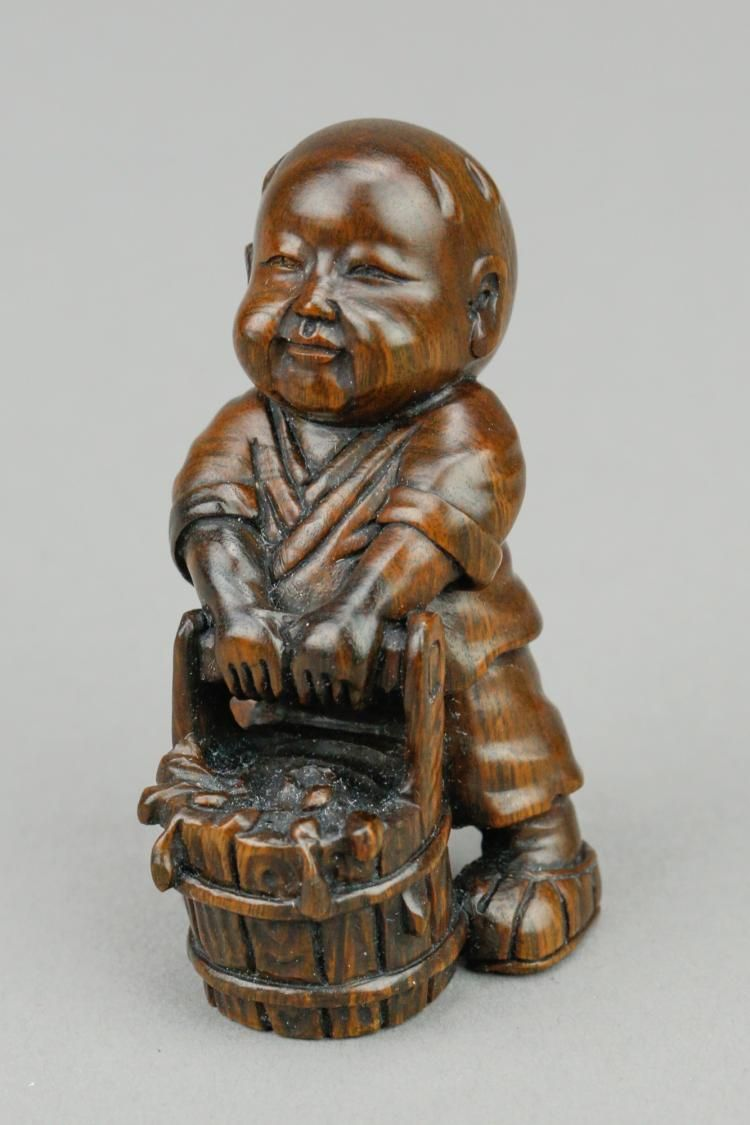 Japanese Boxwood Netsuke Featuring A Child Lifting A