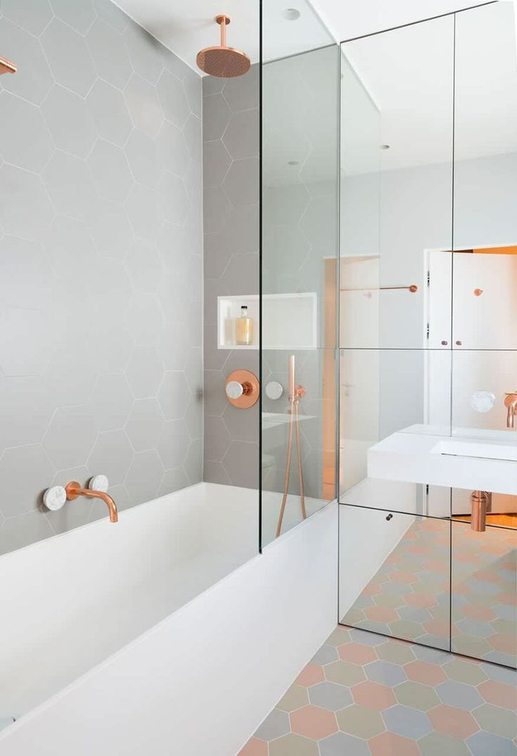 This bathroom features copper and marble fixtures next to light gray ...