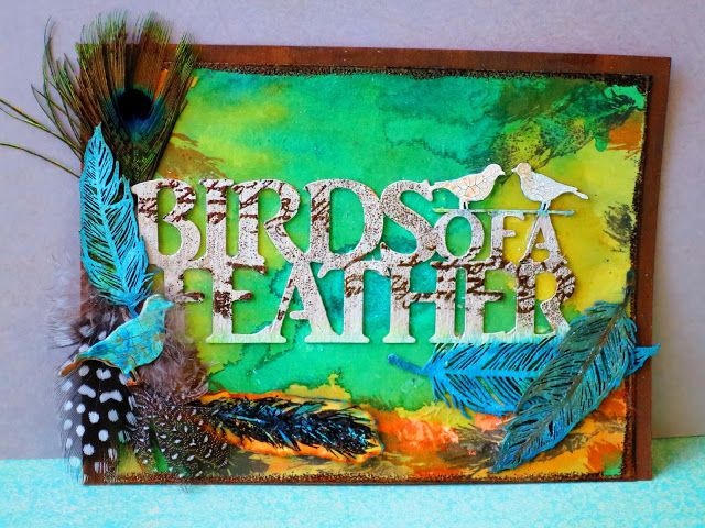 Mixed Media piece using watercolors, #Lindy'sStampGang Sprays&embossing powders,stamps,chipboard and real found feathers