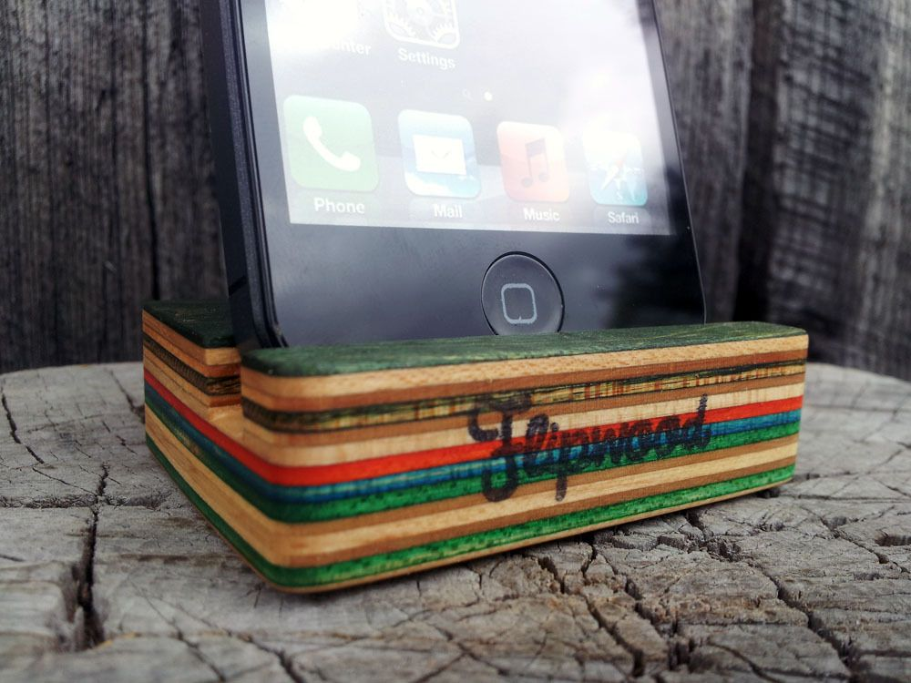 Made by hand from 100% recycled skateboards, this stand holds your smartphone at a comfortable viewing angle in either portrait or landscape mode.  Each stand is cut to order and measures roughly 2 x 2.5 inches, features a limited color scheme and hand stamped logo. All products are finished with organic linseed oil.