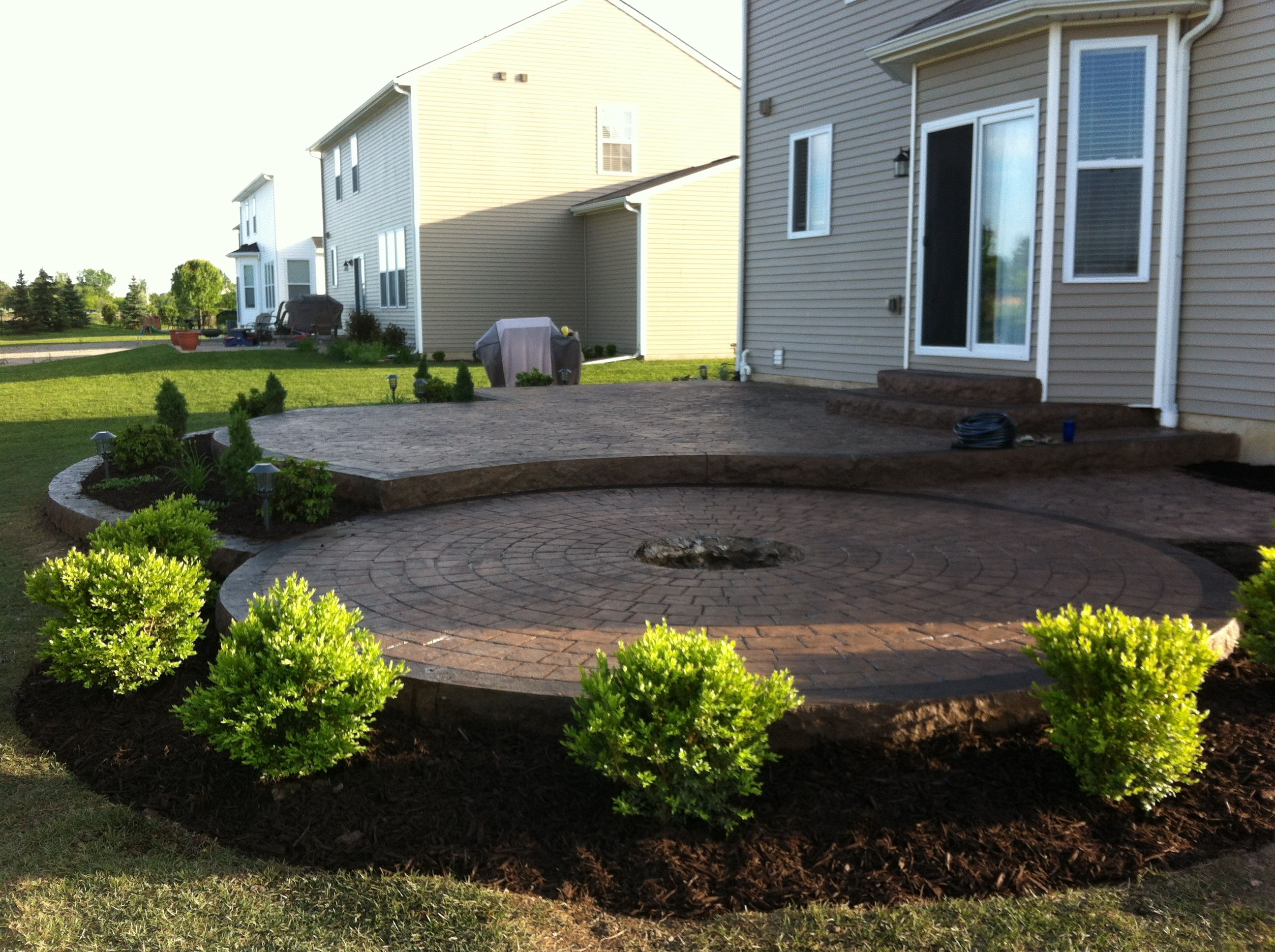 Stamped Concrete Patio two levels with a fire pit ring