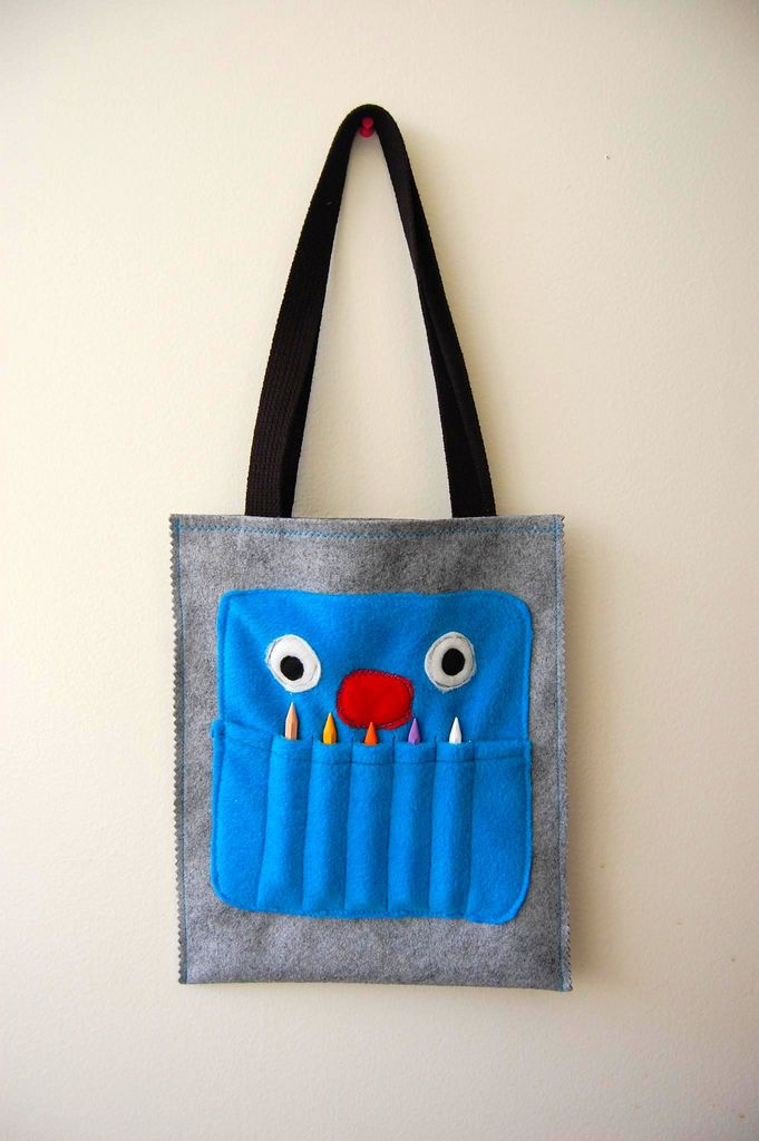 """CRAYON MONSTER ART TOTE TUTORIAL  Favor bags         SUPPLIES  for the monster:  (1) 8"""" x 8"""" piece of fleece for head  (1) 5"""" x 8"""" piece of fleece for mouth  (2) 1.5"""" circles of white fleece or felt for eyes  (2) .5"""" circles of black fleece or felt for eyes  (1) 1.5"""" x 1"""" oval of fleece or felt for nose  (5) crayons     for tote:  (1) 10.5"""" x 25"""" piece of felt  4 ft. belting for strap    TOOLS  sewing machine  matching and contrasting thread  1"""" wide masking tape  pins  iron  scissors…"""