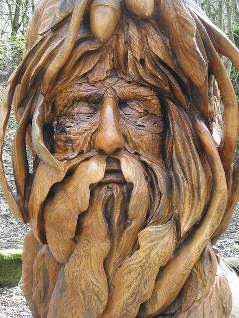 Carved tree man with oak leaves for a beard and acorn