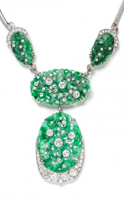 An Art Deco Platinum, White Gold, Jade and Diamond Convertible Necklace, consisting of a detachable central pendant/brooch composed of two pierced and carved mottled white and green oval jade plaques. ~ETS