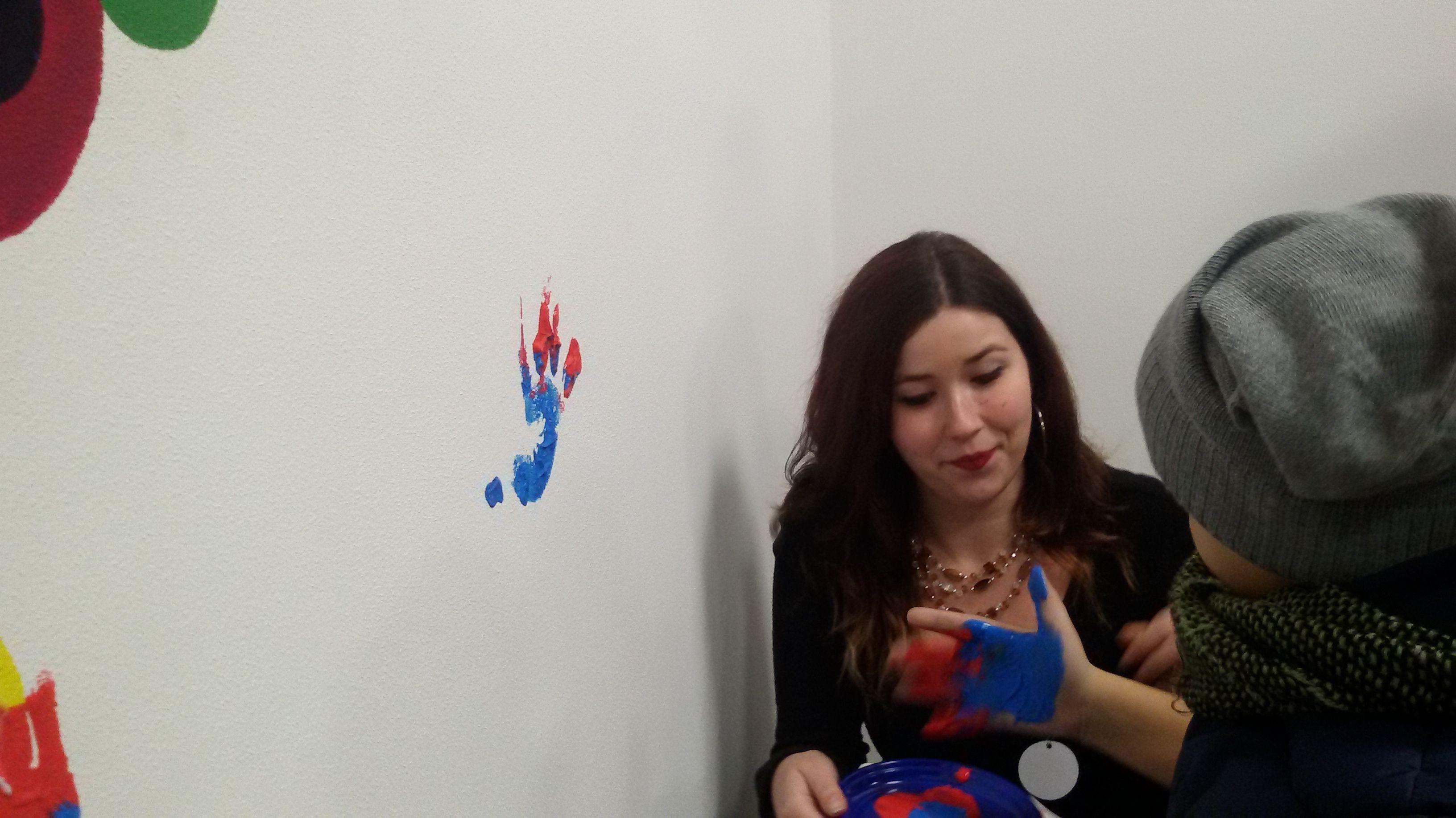 I bambini, con l'aiuto delle studentesse del liceo artistico, lasciano l'impronta delle loro mani sul muro. Liceo artistico Stagio Stagi Pietrasanta