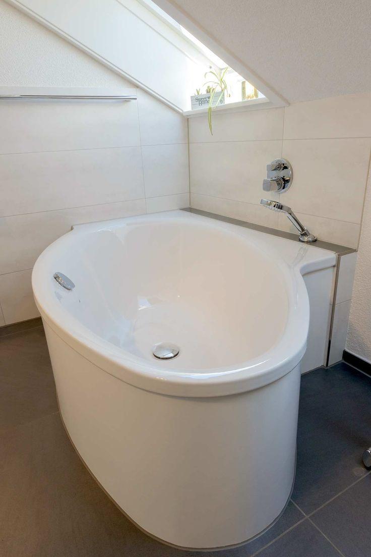 Weiße, freistehende Badewanne mit Wandanschluss, Handbrause ...