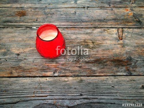 Rot leuchtendes Teelicht auf dem groben Holz einer rustikalen Holzplatte mit Maserung in der Hansaallee von Münster in Westfalen im Münsterland