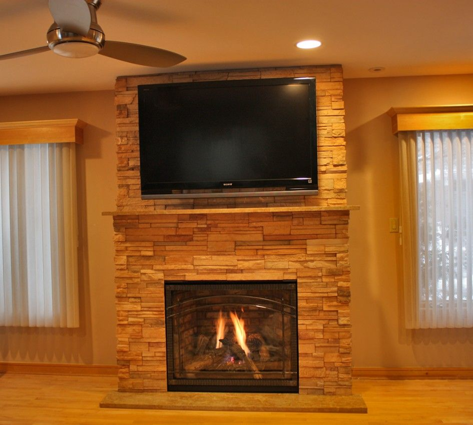 Furniture Exclusive Black Lcd Television Over Gas Fireplace With Stone Surround And Wood Mantel Complete Ceiling Fan Also Laminated Floor