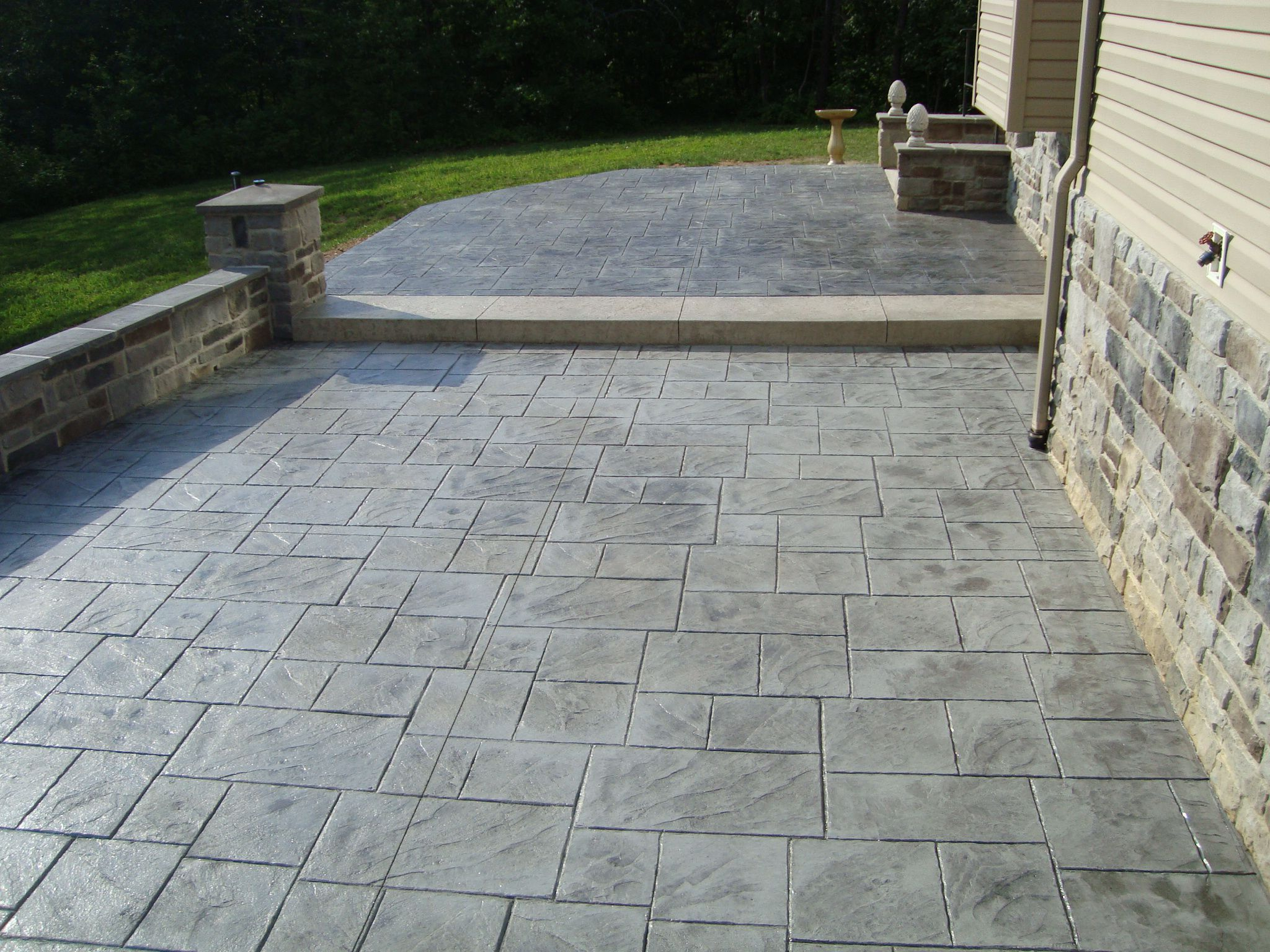 Minimalist Details on Stamped Concrete Patio near Retaining Wall