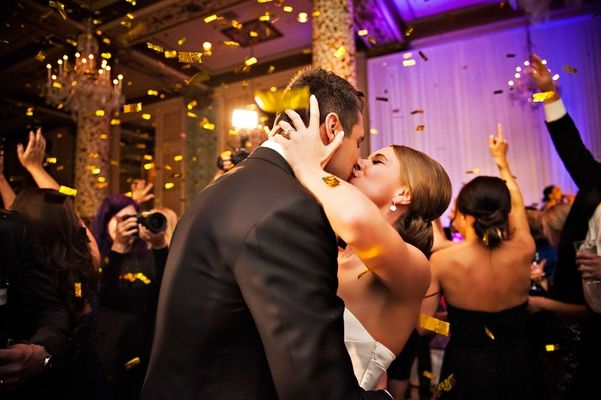 Bride and Groom Kiss Under Confetti    Photography: Carasco Photography   Read More:  http://www.insideweddings.com/weddings/timeless-chicago-wedding-with-gold-details-and-playful-surprises/768/