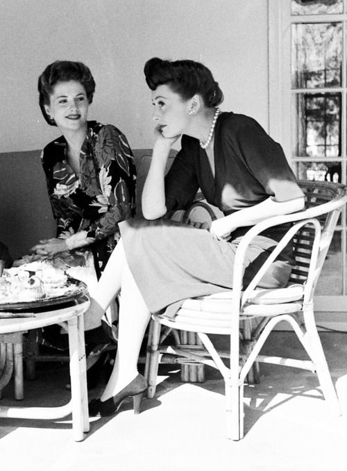 40s Joan Fontaine and Olivia De Havilland taking afternoon tea on the patio. 1942. Found photo vintage fashion style day dress shoes hair movie stars friends WWII era.