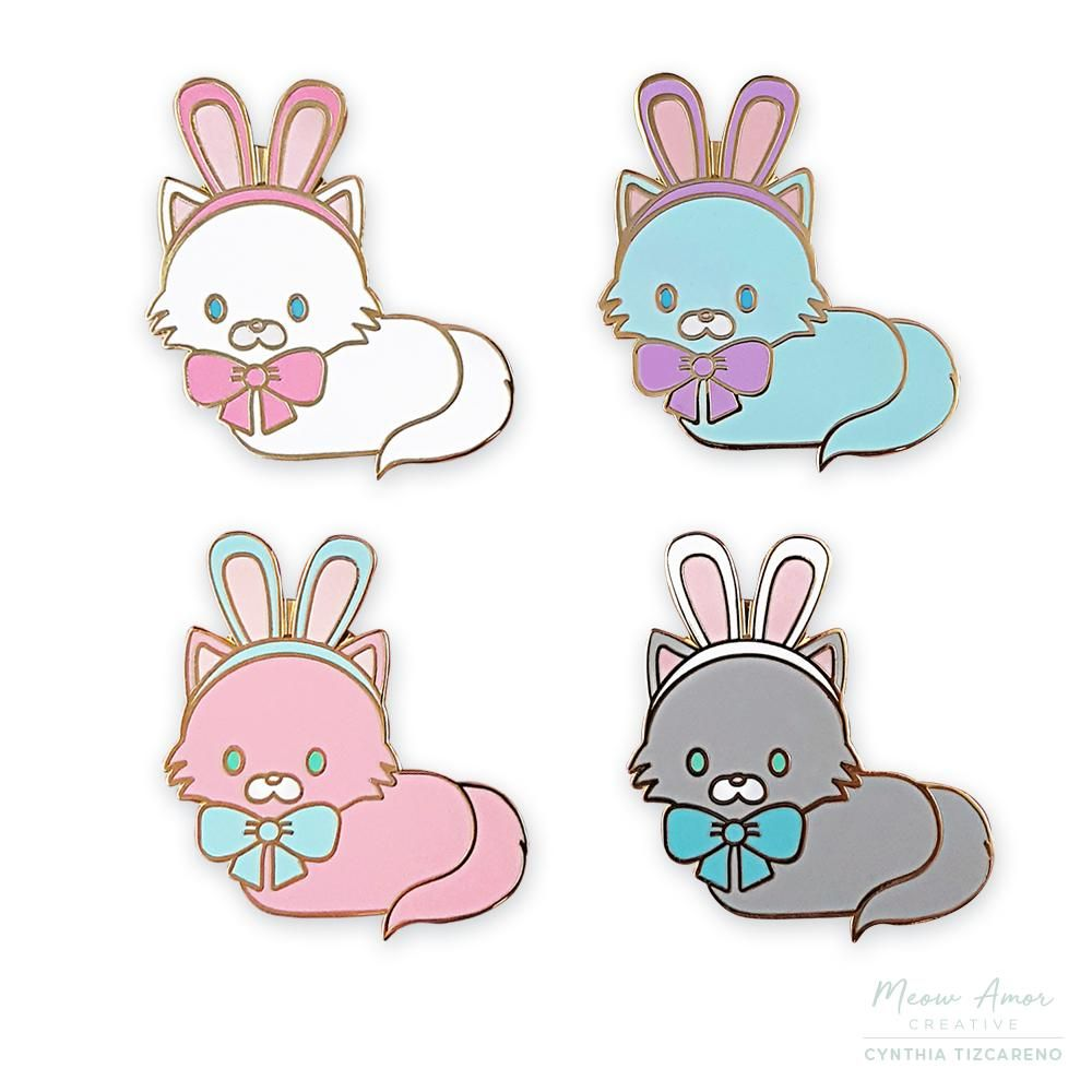 """It's a bunny! Wait its actually a cat pretending to be a bunny! Choose from 4 adorable colors! White kitty with pink bow Light Blue kitty with purple Bow Pink kitty with Light Blue Bow Gray Kitty with Blue bow Details Hard Enamel Pin 1.4"""" Tall Gold Metal rubber clutch"""