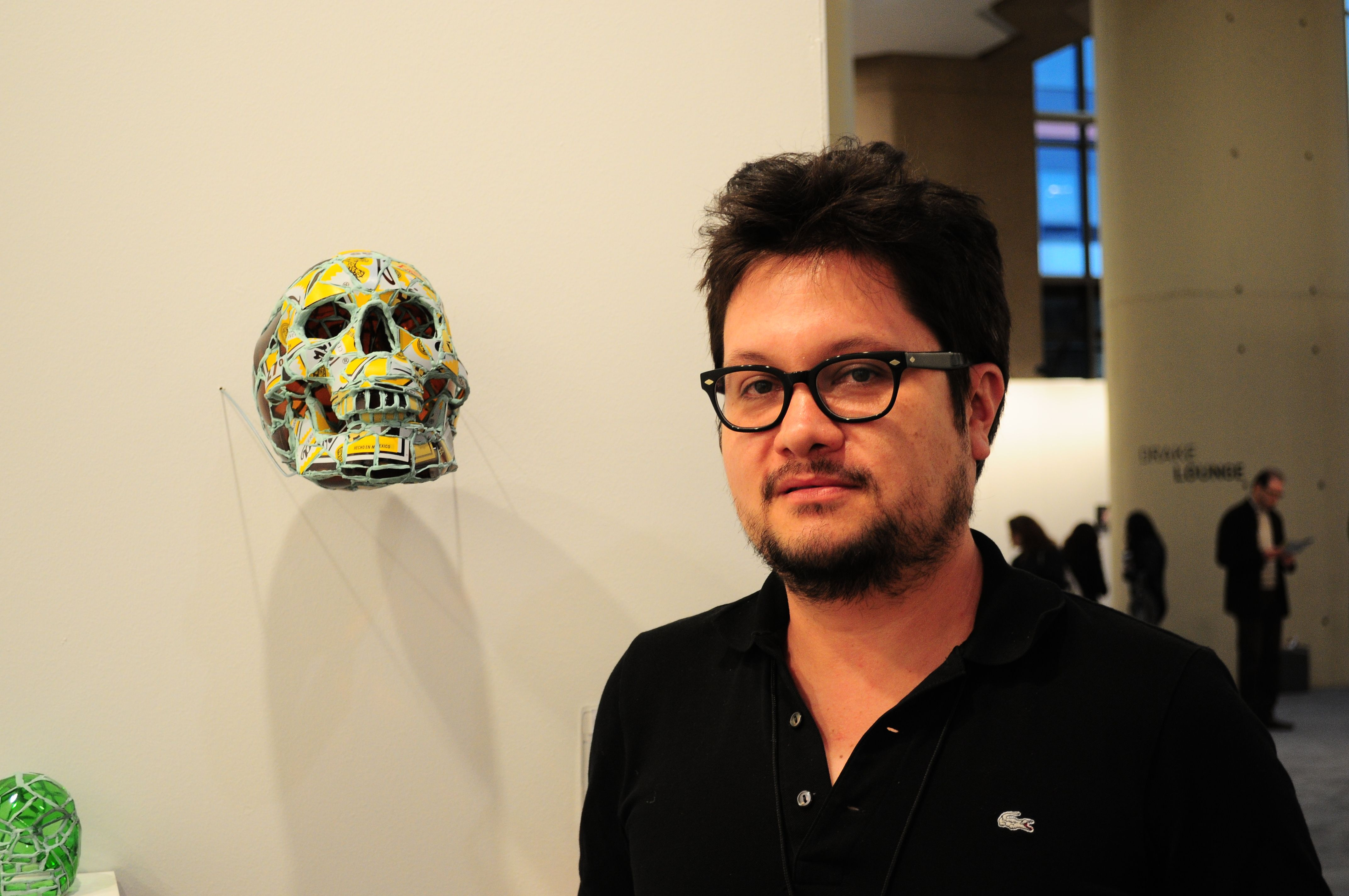 Mexican artist Andres Basurto standing next to his piece Skull.