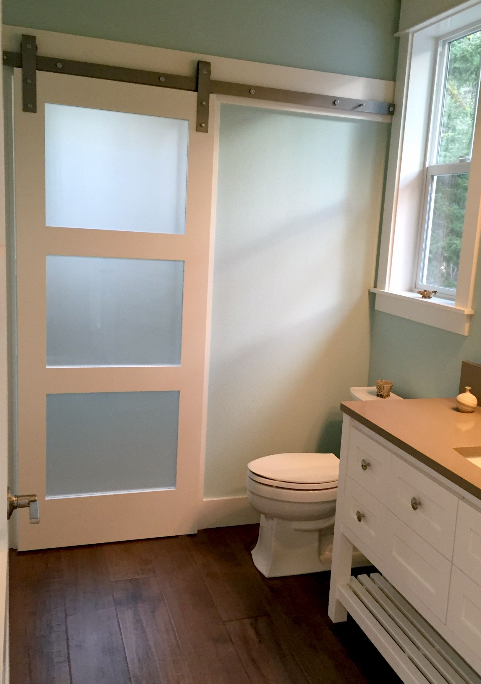 Frosted glass barn door adds privacy to shower room on for Bathroom entrance doors