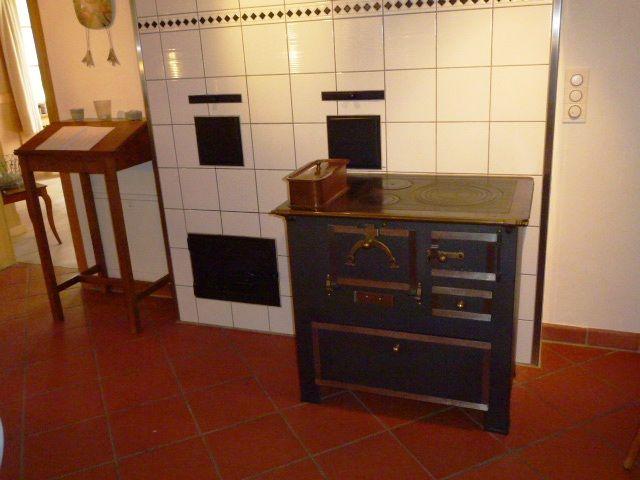 Einheizanlage in der Küche für den Kachelofen im Wohnzimmer Daneben