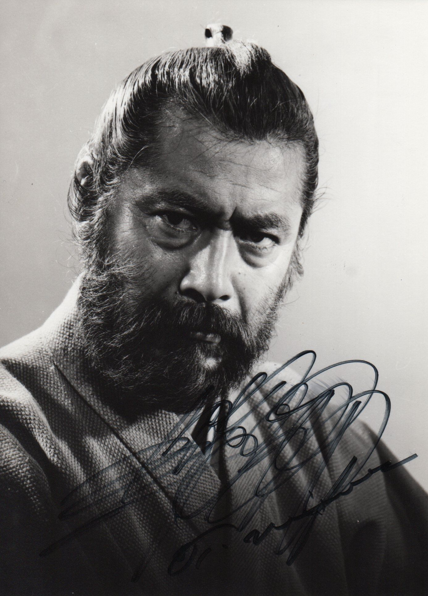 Signed 4½ x 6½ photograph of mifune standing in a head and shoulders pose in costume as a samurai from one of his films