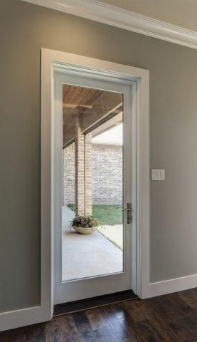 Single White Fiberglass Patio Door With Large Glass View, Clean Trim Frame  The Entrance.