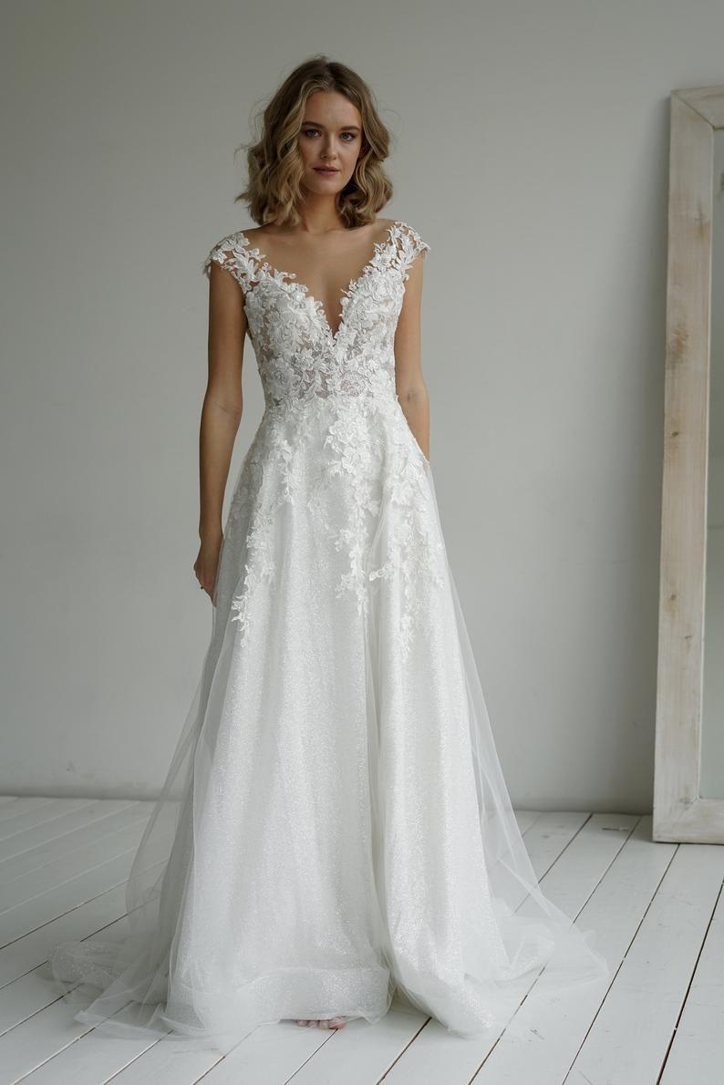 Read the full title Enn by Olivia Bottega Lace Bodice A-Line Wedding Dress | Wedding Dress | Lace Bodice Dress | Glittered Wedding Dress | Wedding Gown