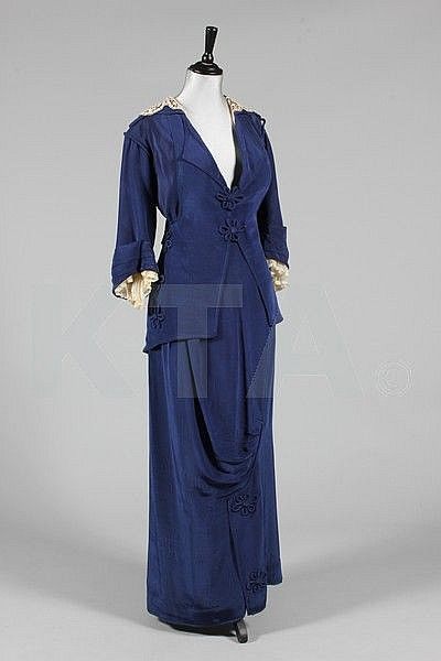 Sapphire blue moiré silk walking suit, circa 1914, the jacket with pointed rear hem, rouleaux frogging fasteners and floral adornments, matching hobble skirt.