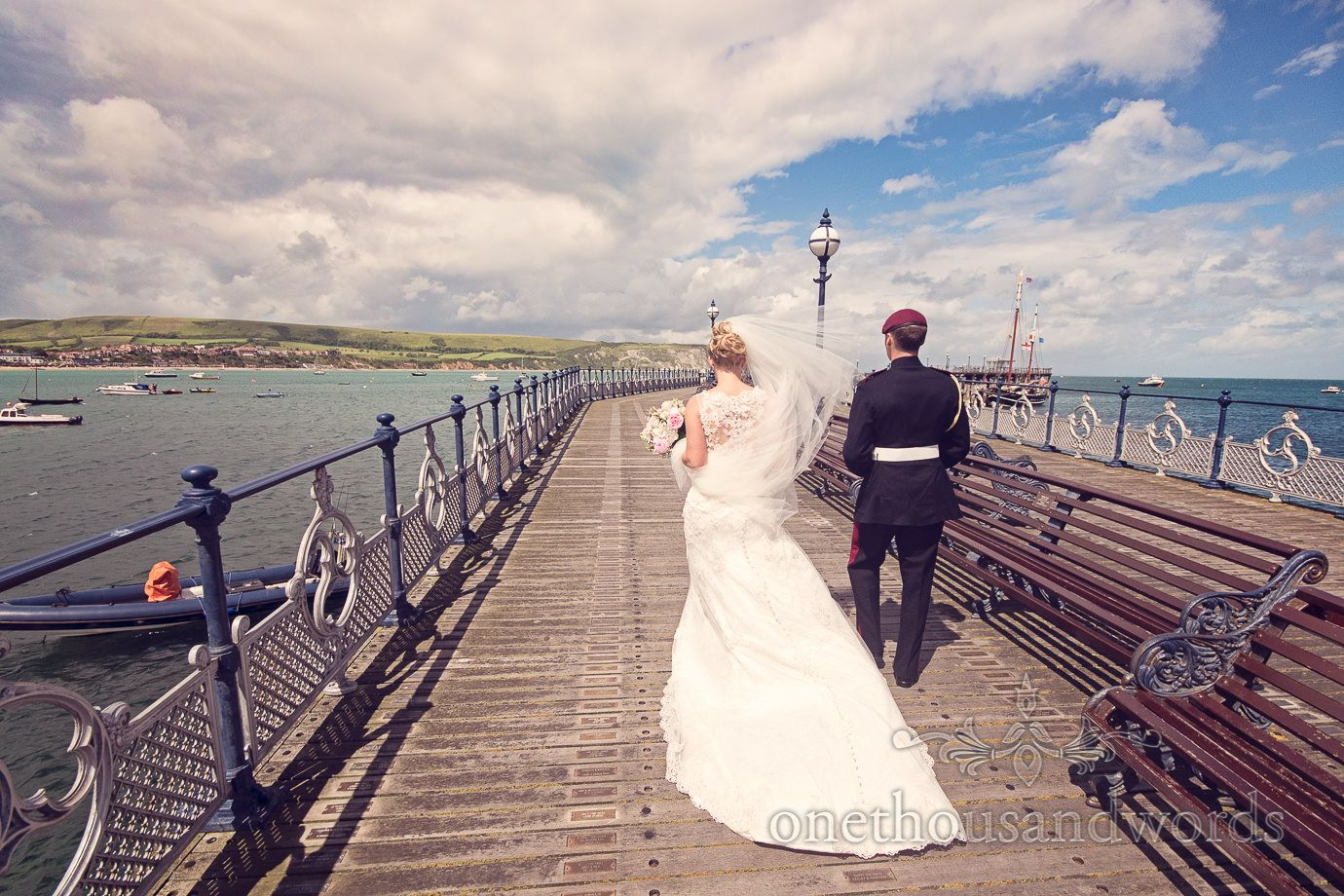 18bde0547a8939 Bride and groom walk along Swanage Victorian Pier wedding photograph.  Photography by one thousand words wedding photographers