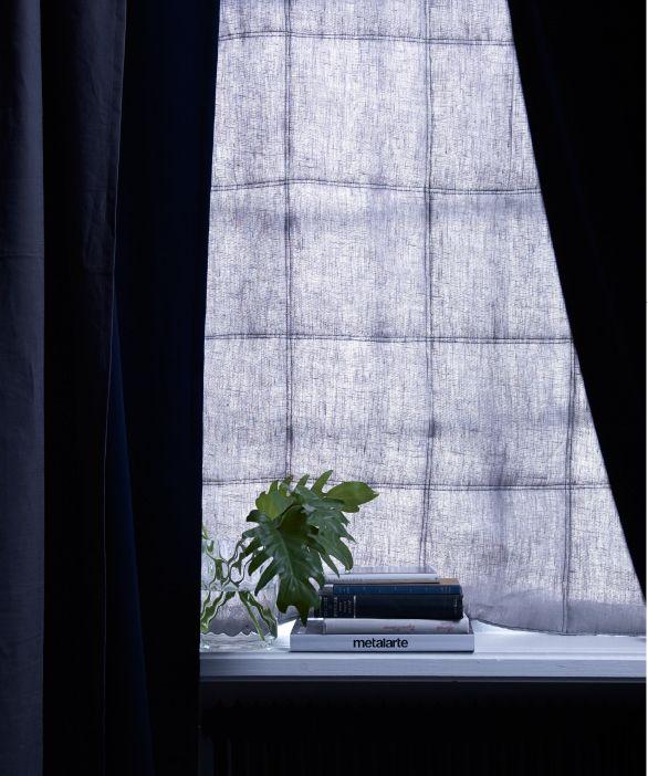 Een donkerblauw geluidswerend gordijn aan het raam houdt zowel het ...