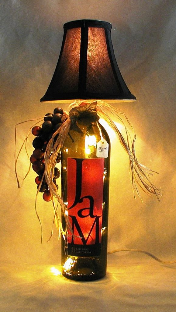 """GORGEOUS WINE BOTTLE LAMP.  This very beautiful lamp has been crafted from a recycled John and Michelle California Red wine bottle.  The bottle is amber and the lamp shade is black.    Lamp is approximately 15"""" tall and approximately 7 """" wide.  It has a nite light under the shade and mini lights inside the bottle.  Comes with a long, switched cord for convenience.  $30.00"""