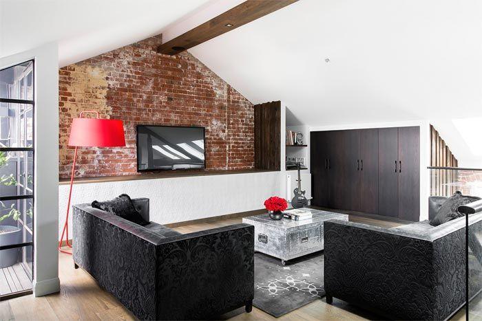 salon abuhardillado pared ladrillo sofas negros - Sofas Negros