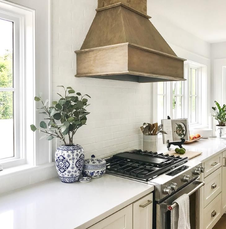 White cottage kitchen with a wood panel French range hood ...