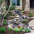 The home's front entrance showcases a beautiful, re-circulating pondless waterfall.      Gardens are not only for lawns and domestic Enjoy fields, but can also be great locations for storage sheds wherein one can just basically stock unused house stuffs from the lose. As Section of the entire household exterior, it is just but proper that backyard garden sheds may even look presentable As well as in-relative to your house's stru... #AquaTerra #easy garden waterfall #OneAcre #pond #Waterfall