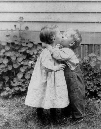 Little kids kissing black and white