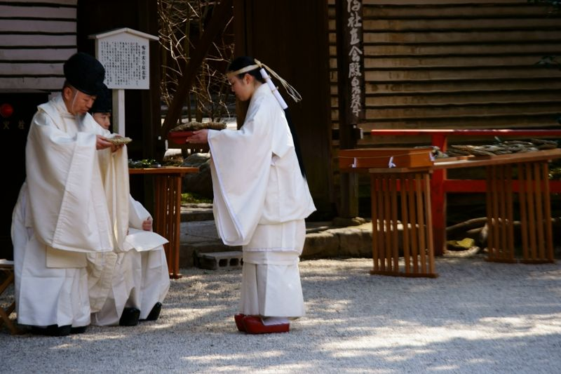 A priest and miko wearing white (signifying purity) junihitoe about to float emperor and empress dolls in a creek flowing through a shrine for the Girls Day holiday.  From  Deep Season