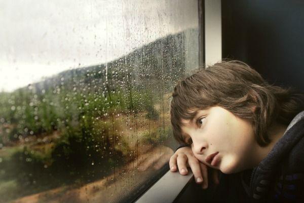 Foto de niño triste mirando por ventana