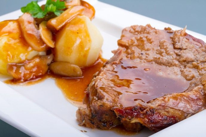 Roast pork with gravy and potatoes on the plate