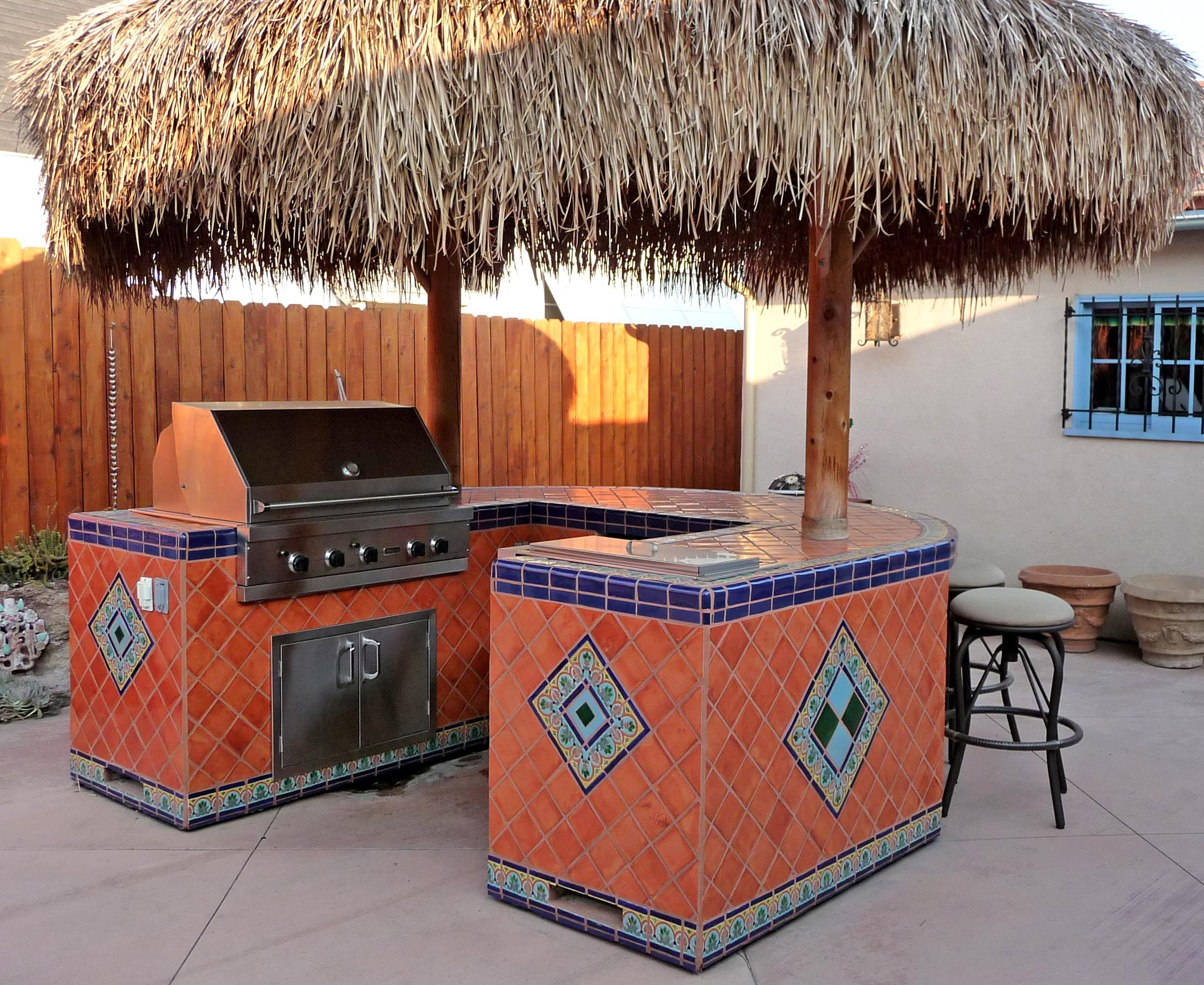Backyard palapa style island barbeque using Mexican tiles by